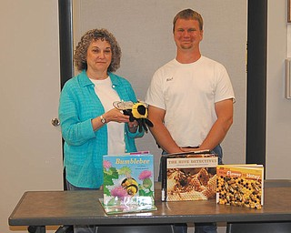 The Trumbull County Beekeepers Association has donated $50 to the Warren-Trumbull County Public Library for the purchase of materials concerning bees for the circulating collection. Jan Vaughn, assistant library director, left, displays the bee hand puppet and four children's books that the gift provided for the library system. The association's vice president, Richard Becker, with Heritage Farm and Apiary in Orwell, Ohio, stands with Vaughn. TCBA meets monthly and can be reached at www.trumbullcountybeekeepers.org. To learn more about the W-TCPL visit www.wtcpl.org.