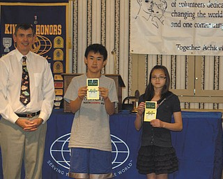 Alan Harper, president of the Kiwanis Club of Youngstown, presents Max Lee, winner of The Vindicator Regional Spelling Bee, and Tamsin Day, runner-up, with gift certificates to Barnes & Noble. The students were honored at the club's weekly luncheon meeting in honor of their spelling achievements. Max is a seventh-grader at Canfield Middle School, and Tamsin is in seventh grade at Willow Creek Leaning Center.