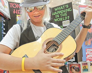 South Range seventh-grader Chris Herubin plays the guitar Tuesday while in character as Tom Petty. All seventh-graders researched projects about musicians who have been inducted into the Rock and Roll Hall of Fame and Museum in Cleveland.
