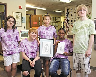 From left, Monica Shirilla, 12,  Cassie Kays, 13, Nazely Rodriguez, 12, Ahmari Bell, 12, and Angus Cadman, 15, all students at the Mollie Kessler School, hold a copy of their cookbook and the picture that was used on the cover.