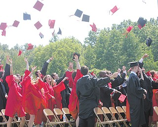 Members of the Canfield High School Class of 2012 throw their caps in elation during commencement exercises Sunday afternoon at the stadium.