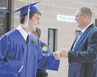 Poland graduate John Bannon gets greeted by assistant basketball coach Rich Black while entering the fieldhouse for commencement exercises Sunday.