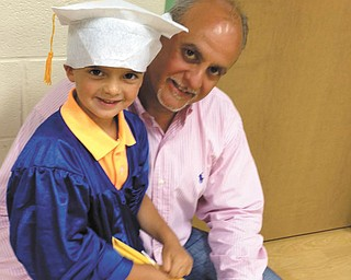 A proud Jim Lipjanic poses with his son, 4-year-old Jimmy Lipjanic, at Jimmy's pre-kindergarten graduation. They are from Boardman.
