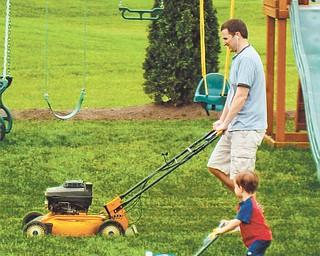 Doug Burns gets some mower help from Owen Burns.