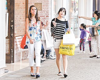 Shoppers walk through the South Shore Mall in Braintree, Mass. U.S. retail sales declined in April and May, pulled down by a sharp drop in gas prices.