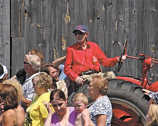 Surrounded by friends and family, Earla Smith sits on a tractor at his farm during a recent celebration staged in honor of the 104-year-old.