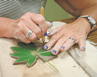 """Colleen Boyle of Youngstown cuts out a leaf she has pressed into clay that will be a decoration on her """"green man"""" wall hanging. Boyle was among students who attended a workshop Tuesday at the D.D. and Velma Davis Education & Visitor Center at Mill Creek MetroParks."""