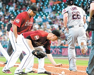 Astros first baseman Carlos Lee, left, and pitcher J.A. Happ watch a bunt by the Indians' Derek Lowe during the  fifth inning of their game Sunday in Houston. The ball stayed fair, and Lowe reached first on the play.