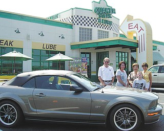 """Mustang and Camaro aficionados will face off Saturday at the Quaker Steak & Lube in Austintown during what is described as """"not your run-of-the-mill"""" car show. At the Fifth Annual Mustang vs. Camaro Showdown, from 10 a.m. to 3 p.m., the public will pick the winner; each vote will cost $1. The top three cars will win trophies. The North Eastern Ohio Camaro Club will pick the best Mustang, and the Mahoning Valley Mustangs will pick the best Camaro. The event raises money for Angels of Easter Seals and will feature a DJ, door prizes, a 50-50 raffle and a basket auction. Car owners will pay a $5 per car minimum donation. From left to right are John Keller, Mustang Club of America director; Betty Keller, vice president of Mahoning Valley Mustangs; Joan Zarlenga, president of Angels; Hunter Crites, Easter Seals client; and Carol O'Neill, of Angels. For information call 330-581-8382 or 330-730-3348. The showdown will go on rain or shine."""