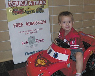 Hunter Estell tries out the Lil' Lightning McQueen 6-volt battery-powered ride-on toy to be given away at the Touch A Truck event Saturday at Village Hall in Poland. Hunter, 3, the son of Robert and Amanda Estell of East Liverpool, is attending the summer preschool session at Rich Center for Autism, where his brother, Greyson, is a student. Employees of Sweeney Chevrolet donated the toy. Raffle tickets for the car, helmet and one-year warranty are $1 and will be sold from 11 a.m. to 2 p.m. All raffle ticket sales and donations made at Touch A Truck benefit the Rich Center. Sponsored by Farmers National Bank, Touch A Truck is a free activity and one of several that are part of the Celebrate Poland festivities. For information visit www.celebratepoland.org.