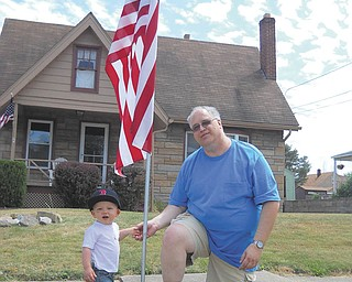 Little Bradley Miller Jr., son of Catherine Cercone and Bradley Miller, helps Tom Baringer, president of Struthers Rotary Club, put the finishing touches on the flag installment at his parents' house. The Rotary club was busy over the weekend filling flag orders for the Fourth of July. The cost is $25, and the Rotary is still taking orders. Contact any member of Struthers Rotary.