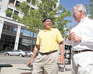 Ron Faniro, left, a local architect, talks with Ed Jerse, director of the Regional Collaboration of Cuyahoga County, during a walking tour of downtown Youngstown. Faniro, of Faniro Architects, served as tour guide Tuesday for members of the Northeast Ohio Sustainable Communities Consortium, who visited portions of the city to get a better understanding of Youngstown.