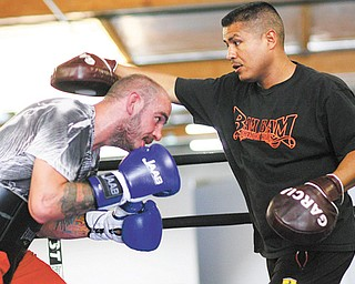 Kelly Pavlik works with trainer Robert Garcia at the Robert Garcia Boxing Academy in preparation for his upcoming 10-round super middleweight bout against Will Rosinsky of New York.