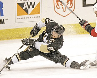 Pittsburgh Penguins' Sidney Crosby shoots the puck from a split after getting by Ottawa Senators' Chris Phillips in the second period of the NHL playoff game in Pittsburgh. Crosby, 24, agreed Thursday to a 12-year contract extension with the Penguins, leaving little doubt that he has overcome concussion like symptoms that sidelined him for most of the last two seasons.