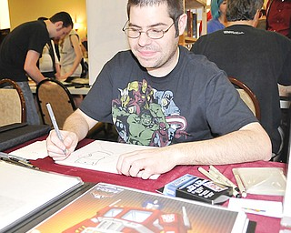 "A.J. Sabino of Kent works on a drawing from the cartoon ""Adventure Time"" during Sunday's All Americon 2012 event at the Comfort Inn in Warren."