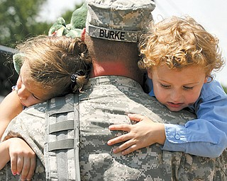 Sgt. Michael Burke of Boardman holds his two children, Maddisen, 5, and Landon, 4, after returning home from a yearlong tour in Kuwait.