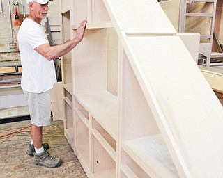 A wooden cabinet is inspected by Andre Silver as it is being prepared for staining. Silver has put his mark on many custom kitchens, cabinets, dens and just about anything made of wood.