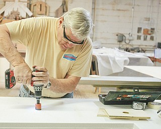 Working on a custom countertop, Rick Fitch drills slowly at Andre Silver's Cabinet Makers on Market Street in Youngstown.