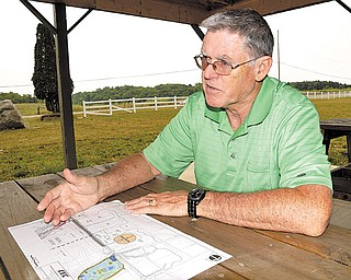 Mike Heher, park board president, shows off the blueprints for the enhancements that will include a drainage pipe.