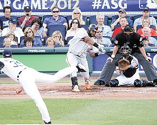 The National League's Pablo Sandoval, of the San Francisco Giants, hits a three-run triple on a pitch by the American League's Justin Verlander, of the Detroit Tigers, in the first inning of the MLB All-Star game Tuesday in Kansas City, Mo.