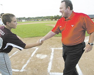 Steve Gillispie, YSU's new baseball coach, shakes hands with Boardman catcher Dominic Pecchia after throwing out the first pitch on Wednesday at the Little League district championship game. Boardman defeated Austintown, 12-11, to earn a trip to state.