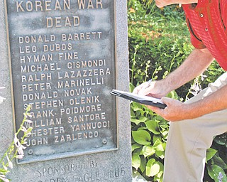 Jerry Nunziato, a retired criminal investigator from Youngstown, writes down names of soldiers from World War II and the Korean War that are listed on the Smoky Hollow Memorial so that he can do research on them.