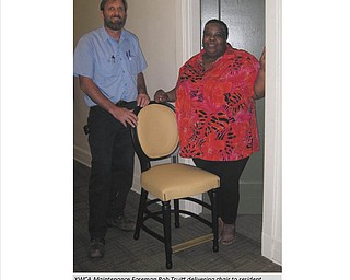 Rob Truitt, YWCA maintenance foreman, delivers a chair from the Gasser Chair Co. to Crystal Williams, a resident in YWCA of Youngstown permanent supportive housing. Mark Gasser, company president, made the donation of 48 chairs for use in YWCA apartments on Rayen Avenue in Youngstown for low-income and homeless individuals. Leah Brooks, interim executive director, said the YWCA recently completed renovation and historic preservation of the YWCA building and the chairs with dark wooden trim and butterscotch color match the historic color palette. The YWCA and community donations help furnish apartments.