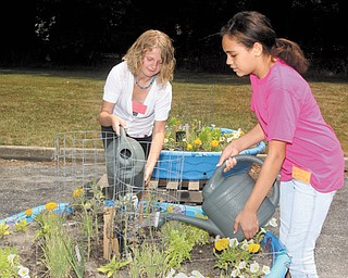 Ashlee Sedmond, left, and Jadyn Atwood, both of Boardman, work on their container garden at Pleasant Grove Presbyterian Church's Camp Newport. Children who attend the Boardman camp participate in a variety of activities and are served lunch. Woodside Elementary in Austintown is host to a sister camp.