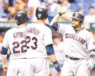Indians slugger Carlos Santana, right, celebrates with teammates Jason Kipnis and Michael Brantley after hitting a seventh-inning three-run home run off Tampa Bay Rays relief pitcher Jake McGee during Wednesday's baseball game in St. Petersburg, Fla. The Indians scored five runs in the seventh to rally past the Rays, 10-6.