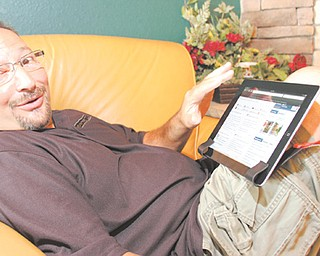 Jerry Balestrino of Hubbard demonstrates the Laptop Trapeze, a device he invented that allows a user to suspend a computer or tablet on their knee. In June, the device won a gold medal at the Invention and New Product Exposition in Pittsburgh for best office supply.