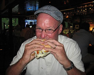 Scott Long takes a bite out of his Pittsburger at the Iron Bridge Inn.