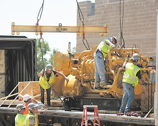 Workers from Diamond Steel of Boardman hook an engine to a crane. The engine will be used to convert methane gas into electricity at the Waste Management Mahoning Landfill in New Springfield.