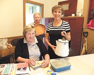 Carolyn Andrews, seated, and Sue Stoddart, left, and Kathy Lepro show some of the artifacts on display at the Upton House, 380 Mahoning Ave. NW, Warren, which is operated by the Harriet Taylor Upton Association. An open house is scheduled from 2 to 5 p.m. Sunday and will feature Waterford items. Carol Olson will host. The house is available for tours and rental for meetings, parties and events. Call 330-395-1840.