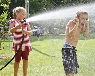 Selena Rockenfelder, 7, sprays Stephen Strawderman, 6, with a hose at the sand sculpture contest at Mill Creek Park. Hoses and sand were provided for the participants.