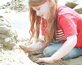 Olivia Lucia, 5, works on her sand castle at the sand sculpture contest at Mill Creek Park.
