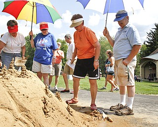(L-R) Ida Krcelic, Louise Zombeck, Gladys Antonelli, and Walter Zombeck stand back to take a look at their sand sculpture at Mill Creek Park on July 29, 2012.
