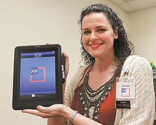 "Aimee Reyes, store manager at J.C. Penney in Southern Park Mall, Boardman, displays an iPad checkout, which associates will use at points throughout the store. J.C. Penney has been in the process of once again reinventing itself by developing its ""Fair and Square Program"" and renovating stores to 