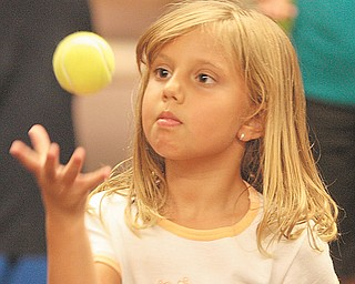 Gianna DeNiro, 6, of Boardman, is focused as she practices her juggling. Raz used the workshop to help the children learn about the laws of motion and gravity.