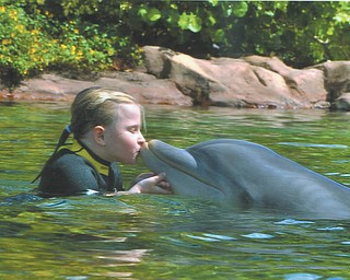 Grace Katherine Burchfield, daughter of Bethany Paulin of New Middletown, celebrates her 7th birthday with the dolphins at Discovery Cove in Florida.