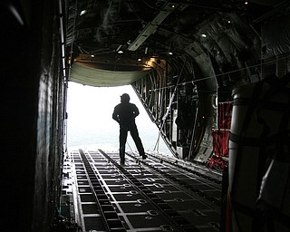 ROBERT K. YOSAY  | THE VINDICATOR..payload exits the back of the C130 H  to a location in the Ravenna Arsenal -  as Sgt James Hudson Watches the  parachute open - .-30-