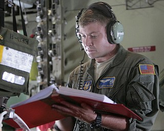ROBERT K. YOSAY  | THE VINDICATOR..SRA Marcus Watson  checks a manifest in the plane - - .-30-