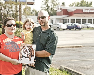 Brook, Marley, 2, and Paul Jillings of Boise, Idaho, hold a photo of their stolen English bulldog, Mabel, who was stolen from the travelers' van at Bob Evans on Belmont Avenue in Liberty.