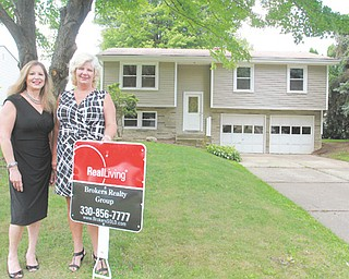 The National Association of Home Builders has ranked the Youngstown metro area as the most-affordable market in which to buy a house in the second quarter. From left, Lynda Cononico and Yvonne Smith of Real Living Brokers Realty Group stand before their latest listing on Elm Trace Street in Austintown.