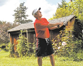 Leland Musguire chips in the backyard of his home in Pulaski, Pa. Musguire has had many hobbies, ranging from boxing to male dancing, and now he is up for Greatest Golfer.