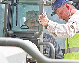Reinhard Schmidt sits in a work vehicle while Master Sgt. Mike Brady shows him how it all works.