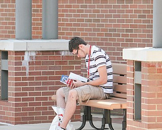 Jacob Schriner-Briggs of Liberty, a freshman at Youngstown State University, looks over his books and supplies in preparation for the start of the fall semester today.