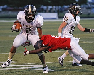 ROBERT  K.  YOSAY  | THE VINDICATOR --..Breaking a tackle on a long run in the second quarter is Hardings #2 Jalyn Powell as Fitchs #9  Keith Lawrence  tries to wrap him up .behind him is #12   Kevin Vingle ( harding 0..Warren Harding @ Austintown Fitch -Fitch Stadium...(AP Photo/The Vindicator, Robert K. Yosay)