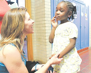 Paris Yanno shares a moment with 4-year-old Bethany Boykin, a student at Heart Reach Ministries day care. Yanno is the ministries director at Heart Reach.