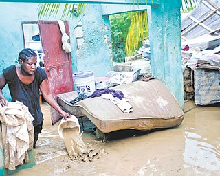 Finanette Guerrier, 29, bails muddy water from her fl ooded house after the passing of Tropical Storm Isaac in Port-au-Prince, Haiti, on Sunday. The death toll in Haiti from the storm has climbed to at least 10 after an initial report of four deaths, the Haitian government said Sunday.