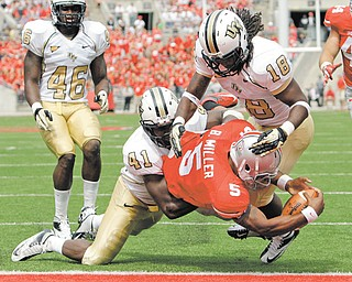 Ohio State's Braxton Miller (5) scores a touchdown between Central Florida's Terrance Plummer, left, and Kemal Ishmael during the third quarter of a game Saturday in Columbus. Ohio State won 31-16.
